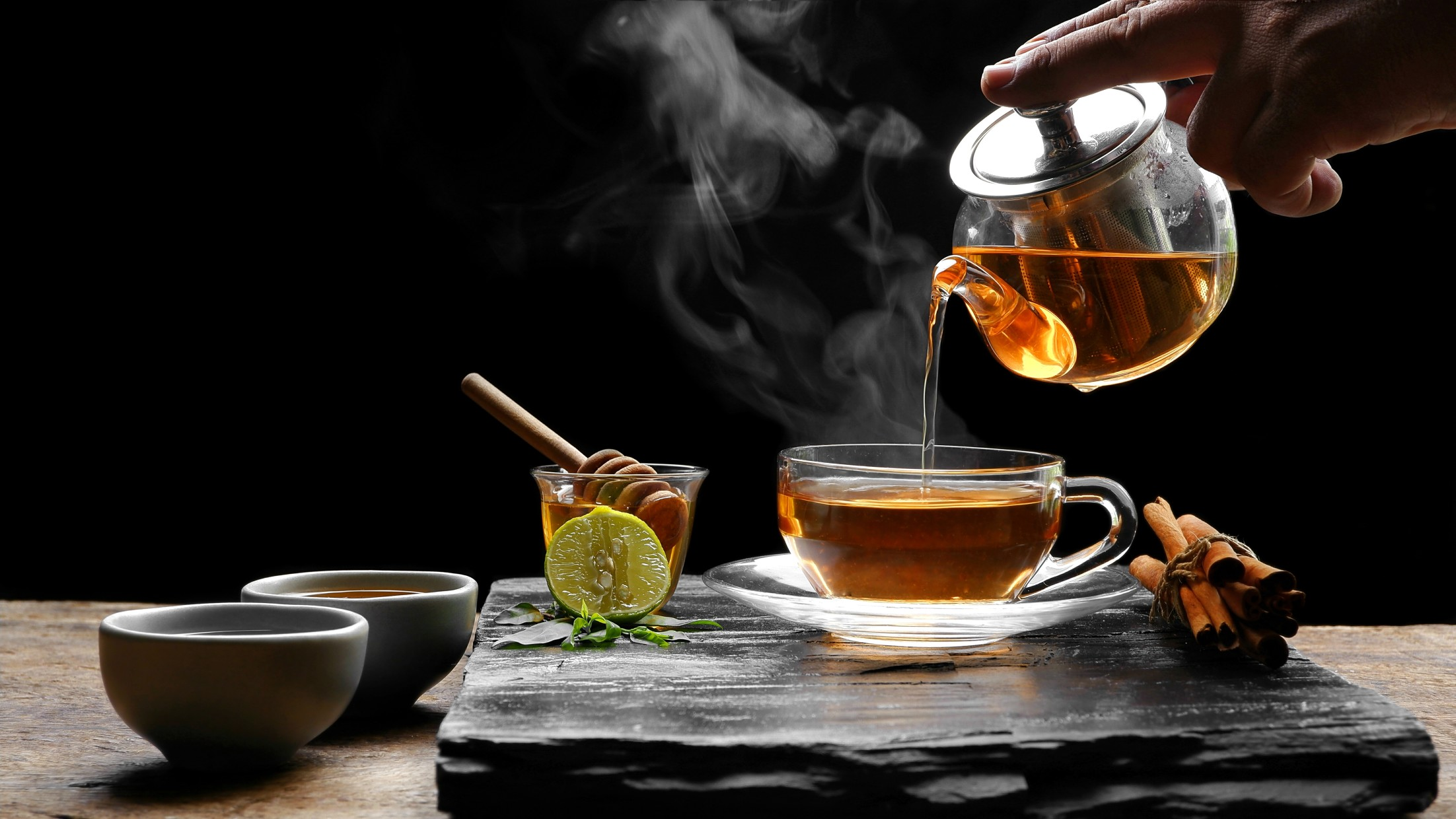 pouring-hot-aromatic-herbal-tea-from-teapot-into-glass-teacup-set-with-steam-and-various-herbs-on_t20_yXbY7a